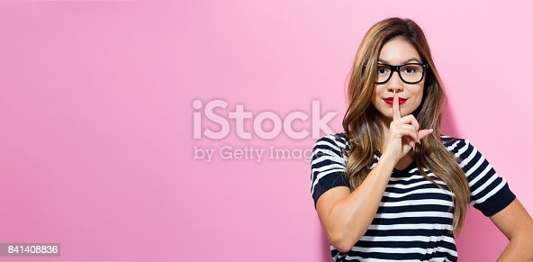 Young woman a quiet gesture on a pink background