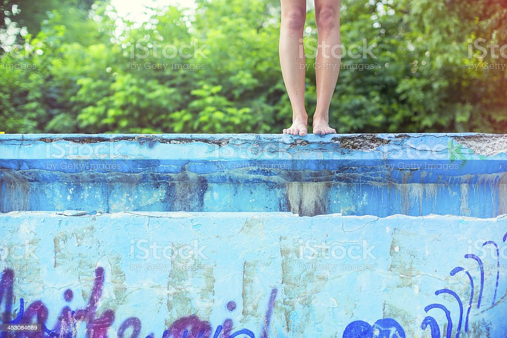 Young woman about to jump into empty old swimming pool royalty-free stock photo