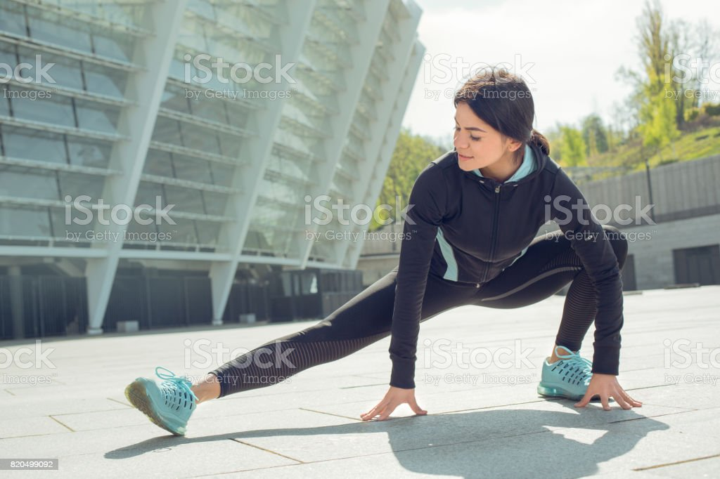 Young woman active exercise workout on street outdoor stock photo