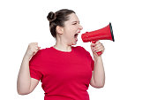 istock Young woman activist in red t-shirt screaming into a megaphone, side view, isolated on white background. 1144601353
