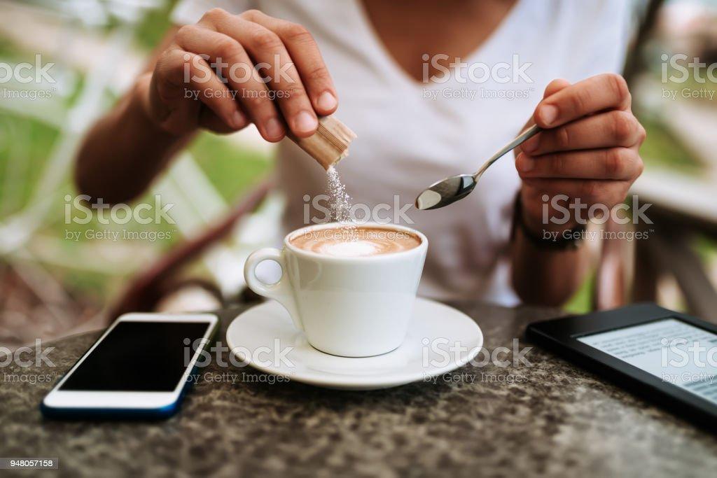 Junge Frau, die den Kaffee weißen Zucker hinzufügen. – Foto