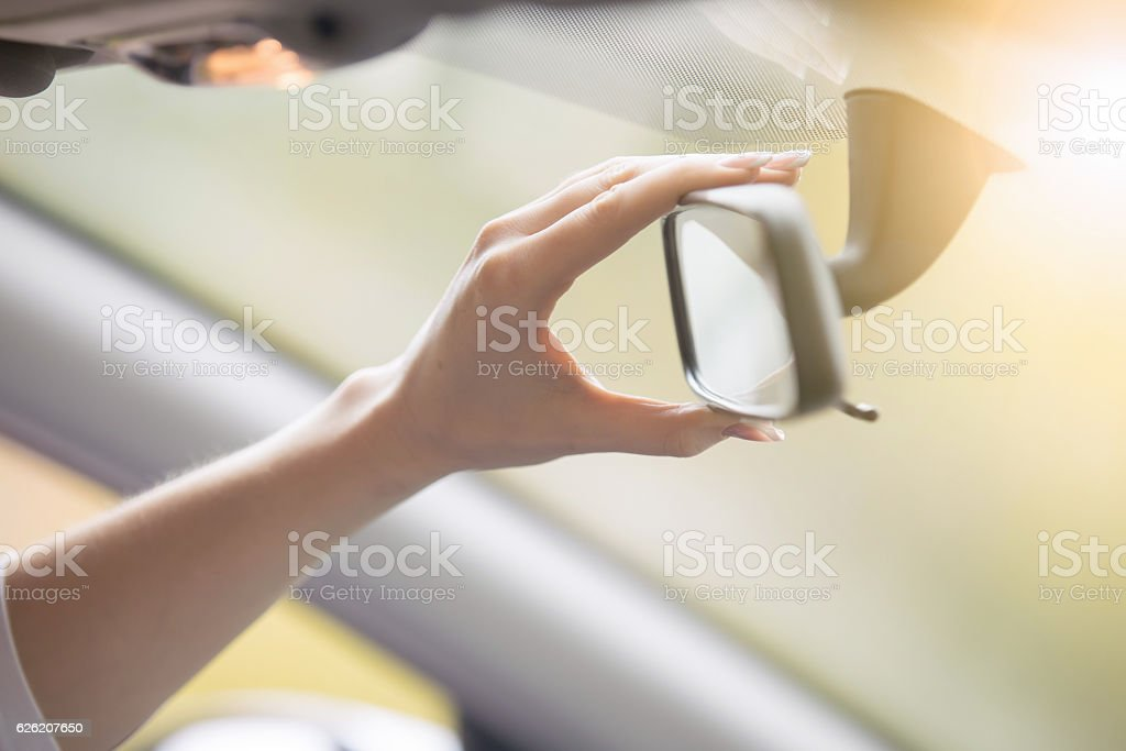 Young woman adjusting a rear-view mirror in the car - foto de acervo