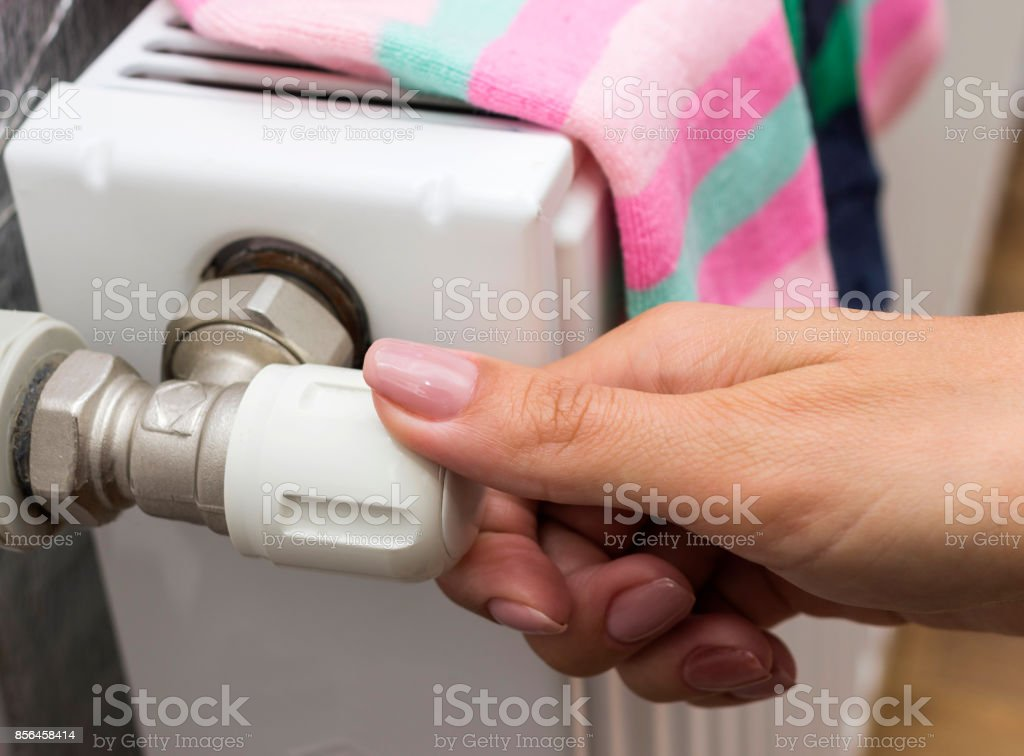 Young woman adjusting the temperature of a radiator. stock photo