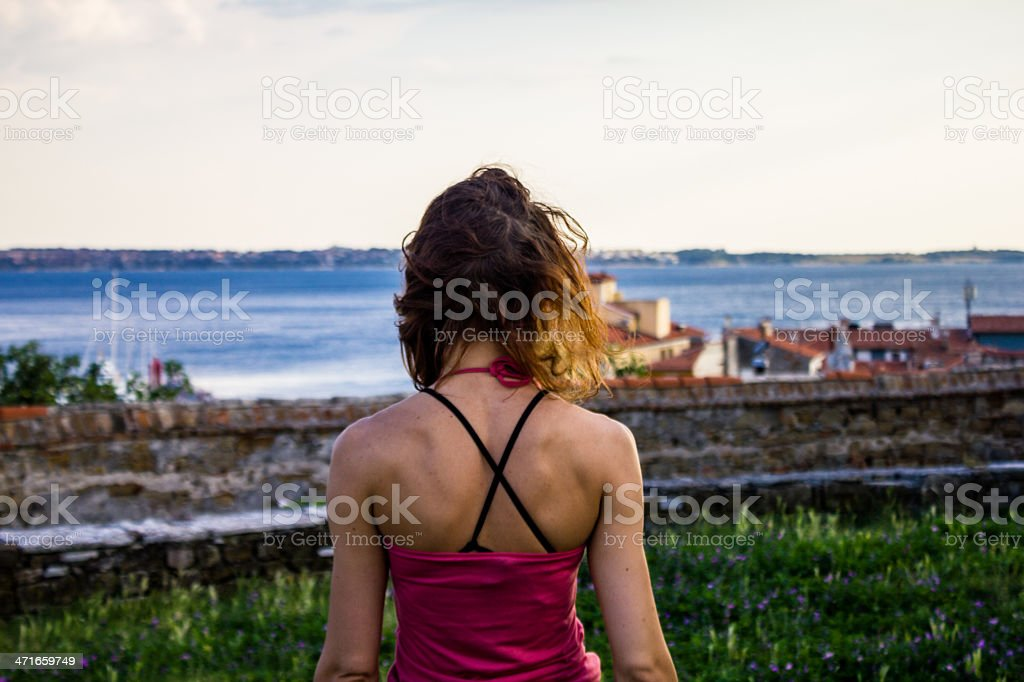 Young woman admiring sea and fishing village royalty-free stock photo