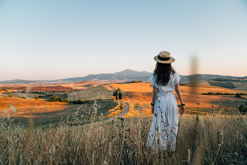 Young woman admiring sunset in a wheat field in Tuscany. She's wearing white clothes and a straw hat.