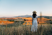 istock Young woman admiring sunset in a wheat field in Tuscany 1262905283