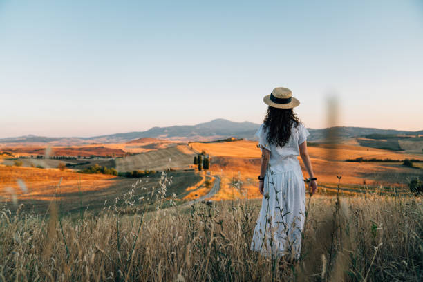 Young woman admiring sunset in a wheat field in Tuscany stock photo
