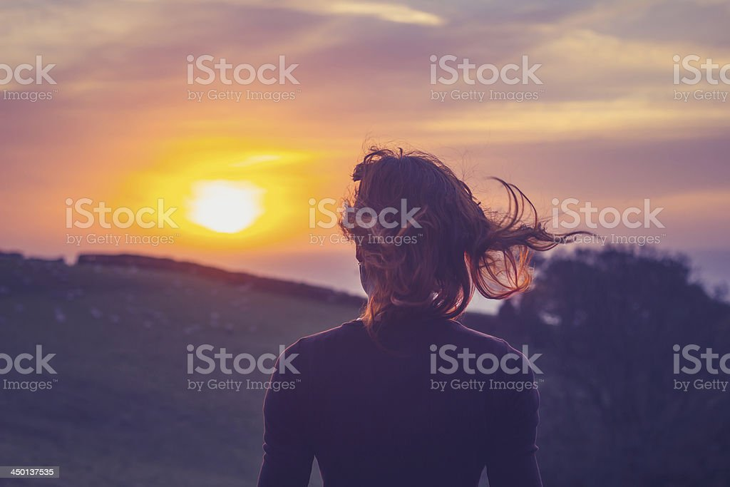 Rear view of young woman admiring the sunset over a field with her...