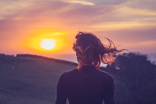 Young woman admiring the sunset over fields stock photo