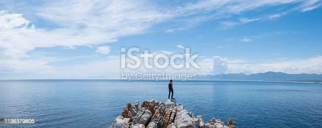 A woman stands on the rocks overlooking the beautiful sea