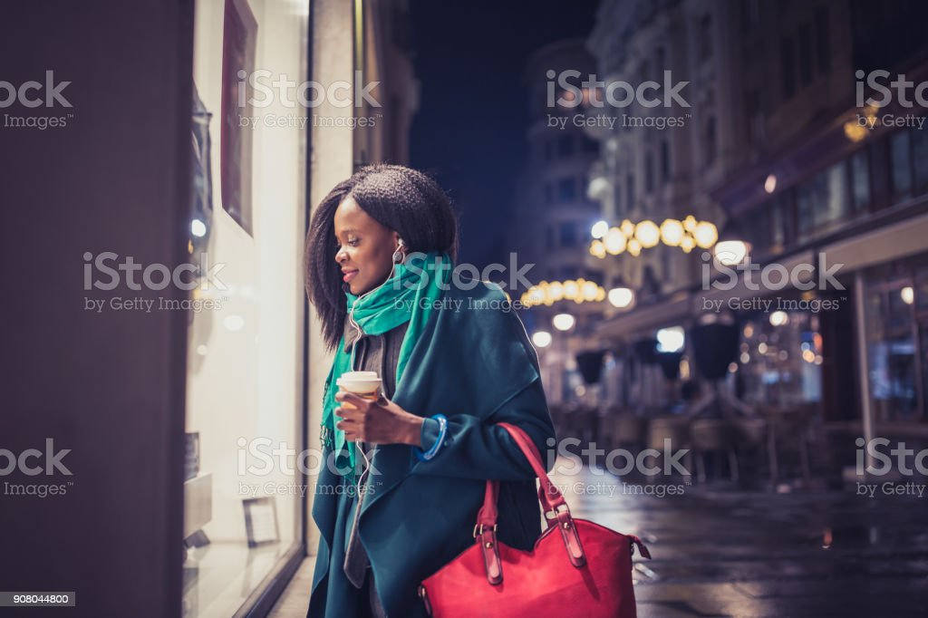 Young woman, African - American ethnicity, looking at the shop window. It's Christmas time stock photo