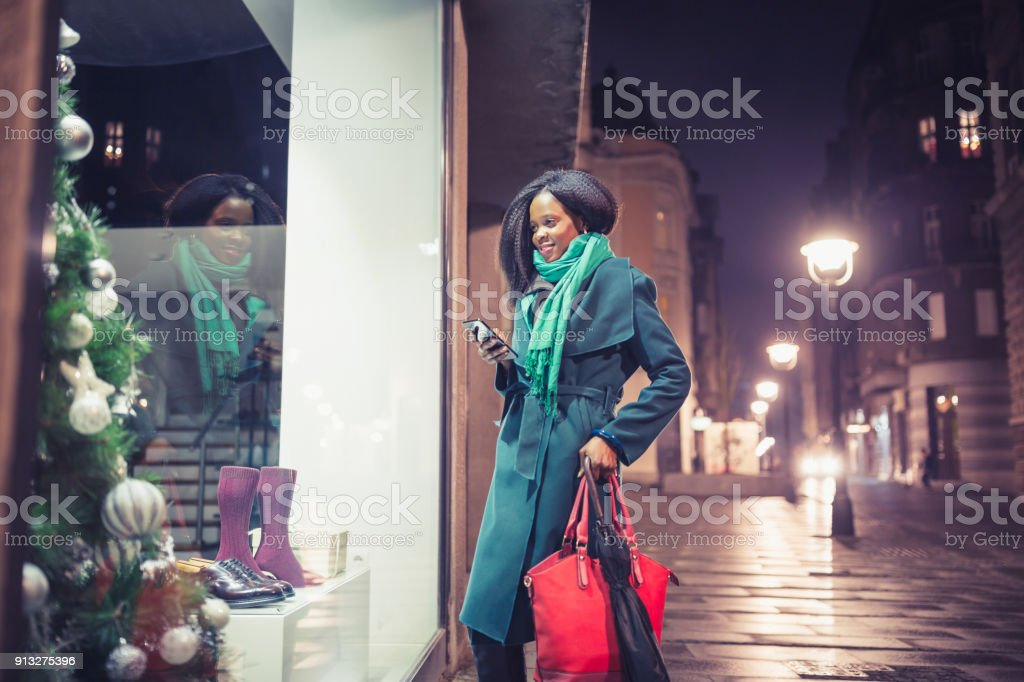 Young woman, African - American ethnicity, looking at the shop...