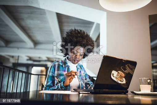 istock Young woman, African-American Ethnicity, drinking coffee and shopping on-line, paying with credit card 911977948