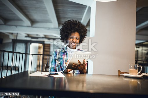 istock Young woman, African-American Ethnicity, using digital tablet in high end restaurant 970078650