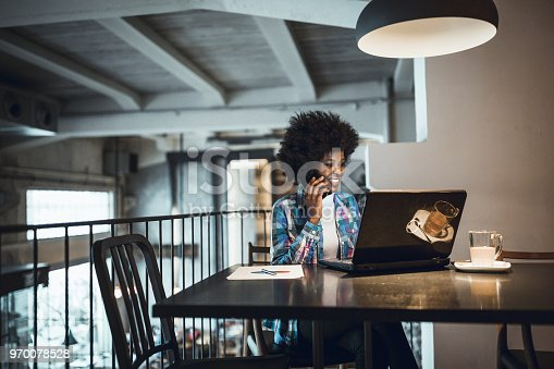 istock Young woman, African-American Ethnicity, working at laptop in cafe, using mobile phone. 970078528