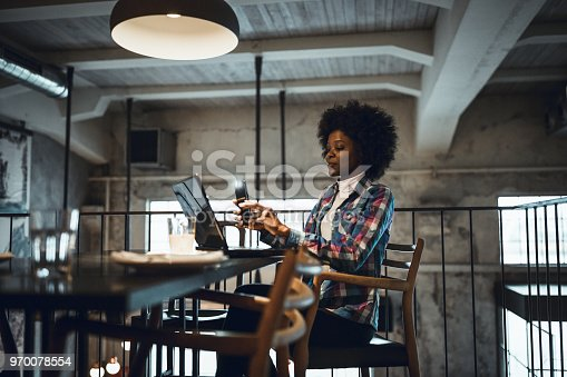 istock Young woman, African-American Ethnicity, working at laptop in cafe, using mobile phone. 970078554