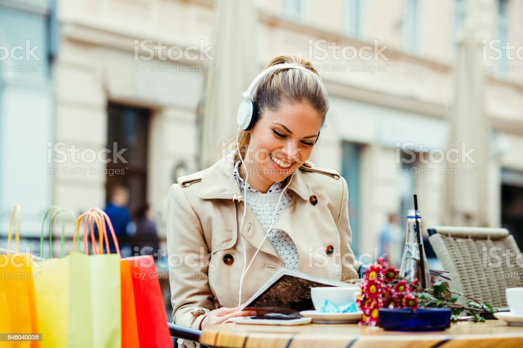 Young woman after shopping reading magazine in a cafe and listen music via headphones stock photo