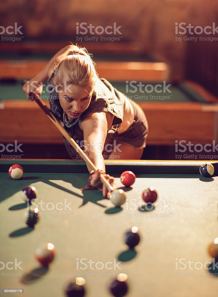 Beautiful woman playing pool game in a pub.
