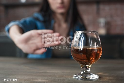 Young female alcoholic social problems sitting at table refusal of alcohol say no to addiction close-up