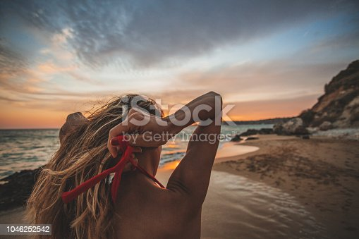 468906855istockphoto Young woman alone during sunset 1046252542