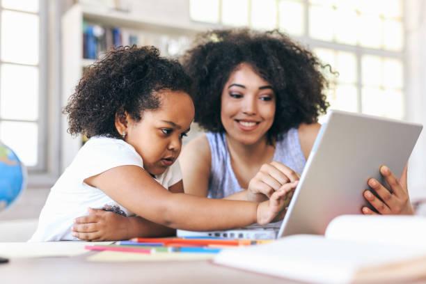 Junge Frau und ein Kind, das auf Laptop zeigt – Foto
