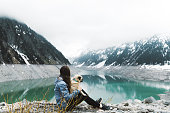 Young smiling woman with long hair in blue jacket and her small fluffy cute pug sitting on her knees resting near turquoise Schlegeis lake and snowcapped mountains in Zillertal Alps