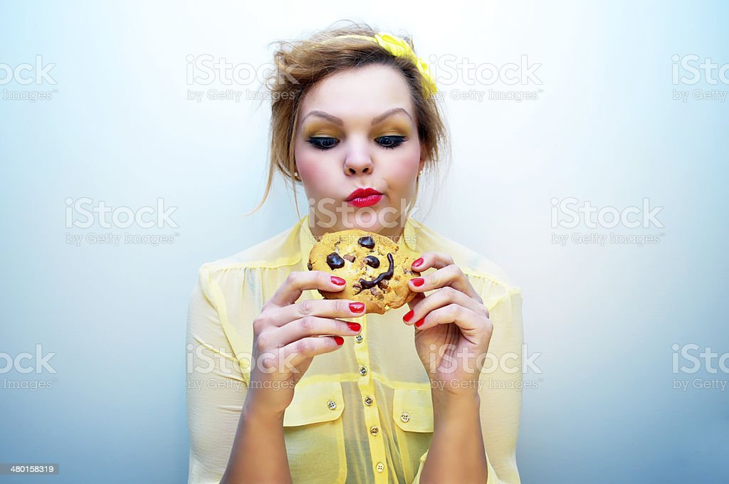 Young woman and a smiling chocolate chip cookie. stock photo