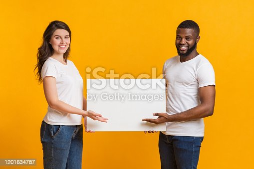 1159989540 istock photo Young woman and afro man holding and pointing at blank placard 1201634787