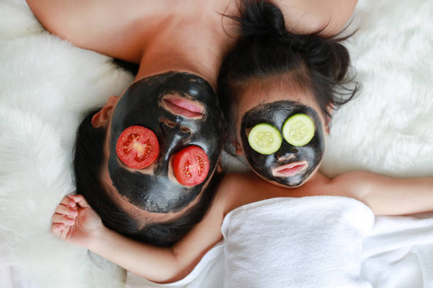 Young woman and child girl in black peeling face mask, beauty concept. stock photo