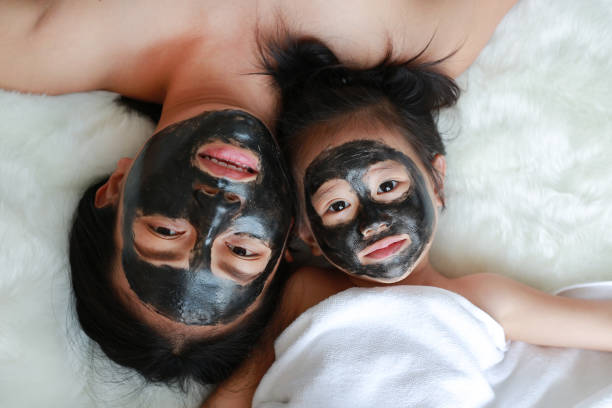 Young woman and child girl in coal peeling face mask, beauty concept. stock photo