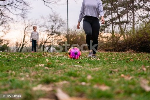 829627936 istock photo Young woman and child playing soccer in park together 1212761243