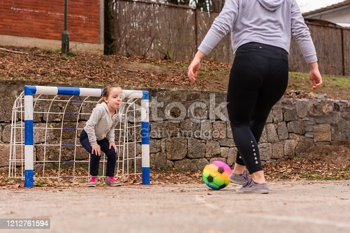 829627936 istock photo Young woman and child playing soccer outdoors 1212761594