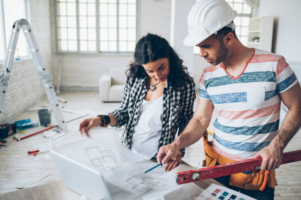 Young woman and construction worker looking at blueprints stock photo