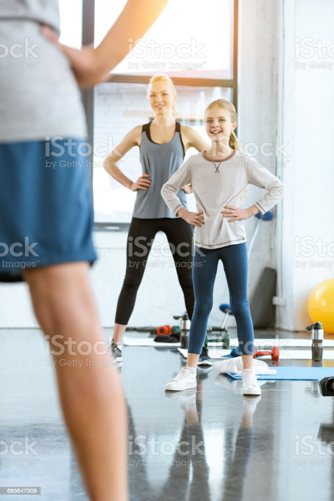 Young woman and cute girl exercising with coach at fitness studio 免版稅 stock photo