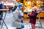 Happy kid girl and young beautiful woman with cup of steaming hot chocolate and mulled wine. Adorable child and beautiful mum on Christmas market in Germany. Family walking on Xmas market
