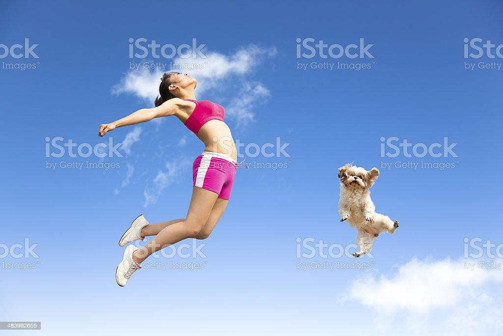 Jeune femme et chien de sauter en l'air - Photo