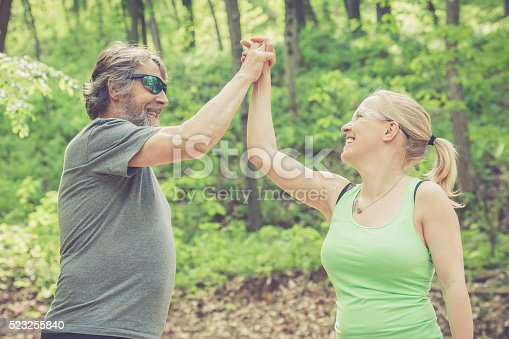 istock Young woman and elderly man in the forest, high five 523255840