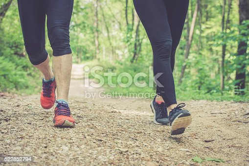 Young blonde caucasian woman and elderly man running in the forest; foot close up, outdoor sport photography, all logos removed.