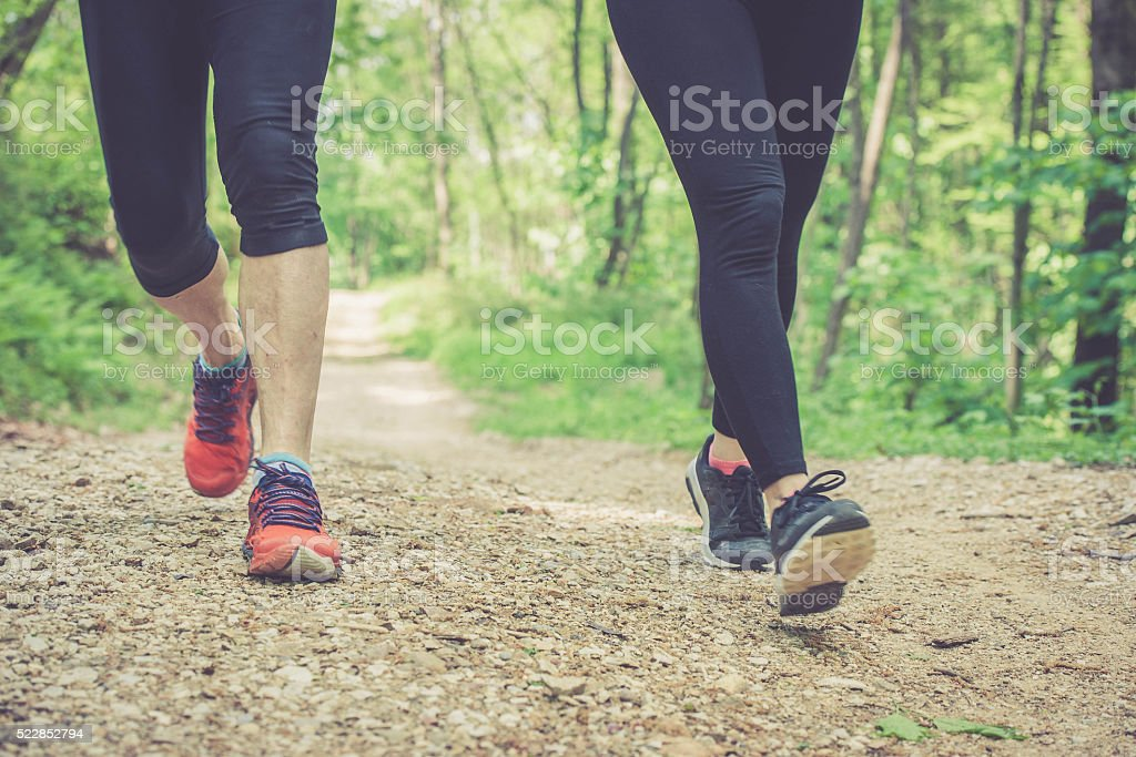 Young woman and elderly man running in forest - foot stock photo