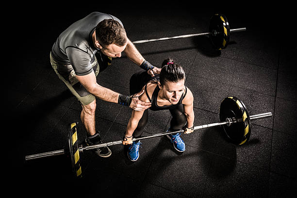 Young woman and fitness instructor on cross training in gym stock photo