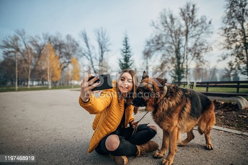 636418612 istock photo Young woman and german shepher in the park taking a selfie 1197468919