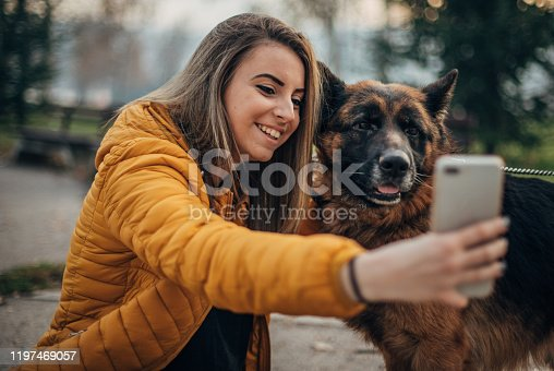 636418612 istock photo Young woman and german shepher in the park taking a selfie 1197469057