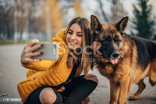 636418612 istock photo Young woman and german shepher in the park taking a selfie 1197469862