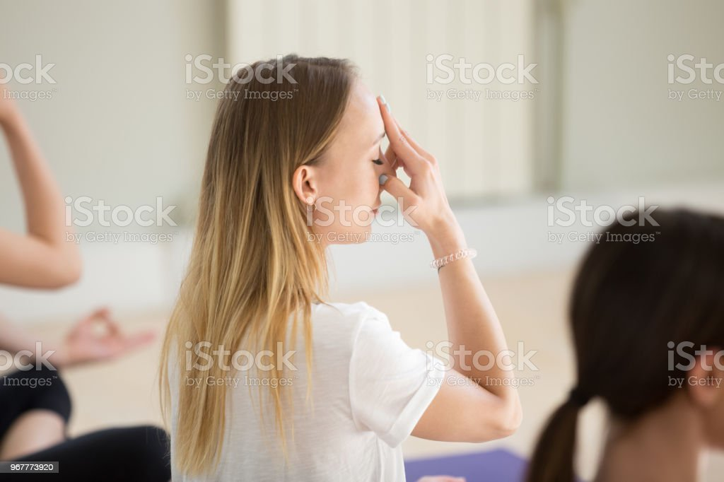 Young woman and group of people doing Alternate Nostril Breathing stock photo