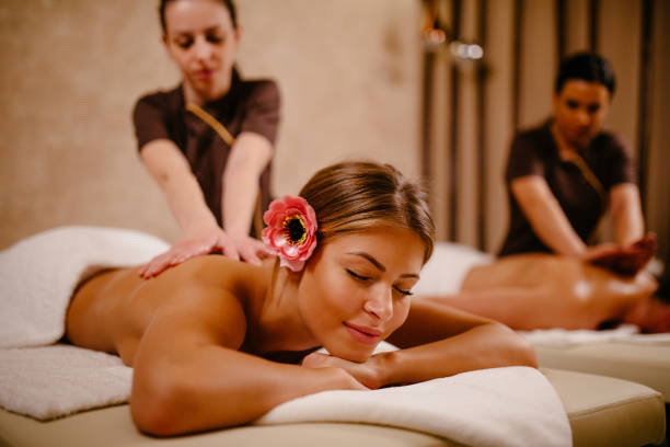 Young woman and her boyfriend having back massage at the spa stock photo