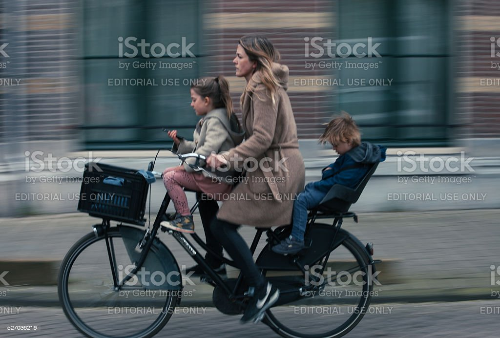 Young woman and her children riding a bicycle in Amsterdam stock photo