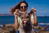 young woman and her cute spanish water dog outdoors enjoying together on a sunny and windy day. Summertime, love for animals and holidays concept