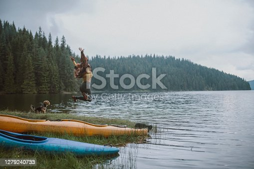 Young cheerful woman is having fun with her terrier dog  in a view of beautiful pine trees and lake