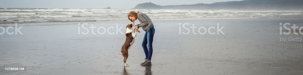 Young woman and her dog on a Northern California beach stock photo