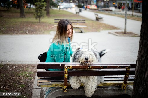 Young woman and her dog resting on wooden bench in park